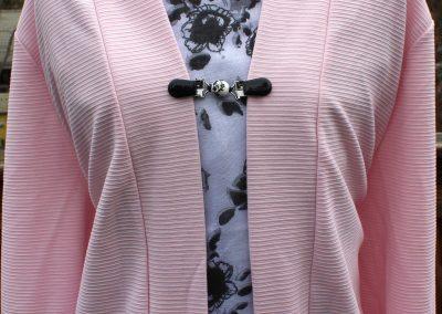 Napittoman neuletakin ja villatakin pidike nimeltä Klipsutin Unna. Kuvassa näkyy tuote käytössä.